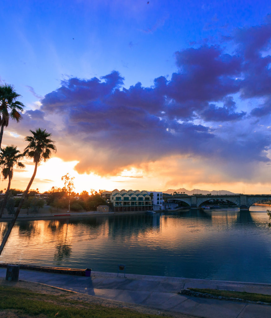 Sunset over Lake Havasu City, Arizona with the London Bridge in the background. Reflections, clouds, and palm trees.